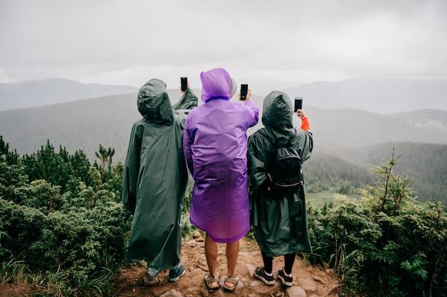 Il gruppo di viaggiatori in impermeabili sta nelle montagne e scatta foto del paesaggio di natura selvaggia sui telefoni. tre turisti fanno seilfie con il telefono in una piovosa giornata estiva
