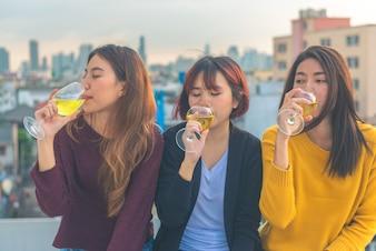 Il gruppo felice di ragazze asiatiche gode della risata e del bicchiere di vino spumante allegro alla festa sul tetto