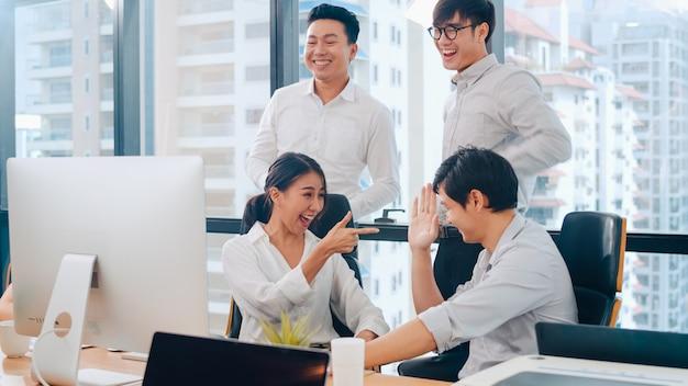 Il gruppo millenario di giovani persone di affari dell'asia l'uomo d'affari e la donna di affari celebra dare cinque dopo avere trattato la sensibilità felice e la firma del contratto o dell'accordo nella sala riunioni in piccolo ufficio moderno.