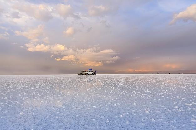 Il gruppo turistico e l'auto sono a salar de uyuni durante il tramonto. belle nuvole nella luce del tramonto. bolivia, sud america
