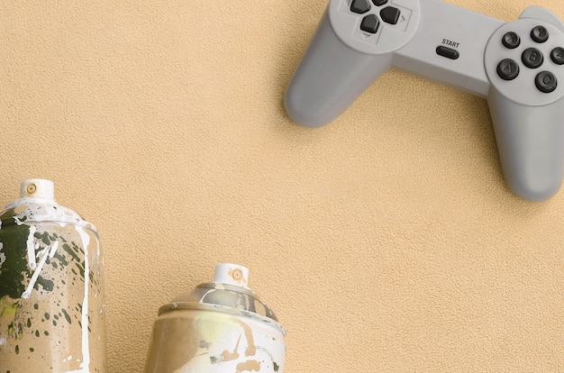 Il joystick e due bombolette spray si trovano sulla coperta in tessuto felpato arancione felpato.