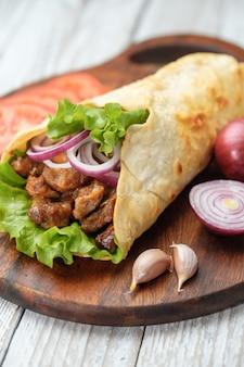 Il kebab di doner giace sul tagliere. shawarma con carne, cipolle, insalata si trova su un vecchio tavolo di legno bianco.