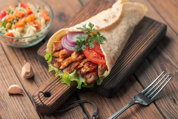 Il kebab di doner giace sul tagliere. shawarma con carne di pollo, cipolle, insalata si trova su un vecchio tavolo di legno scuro.