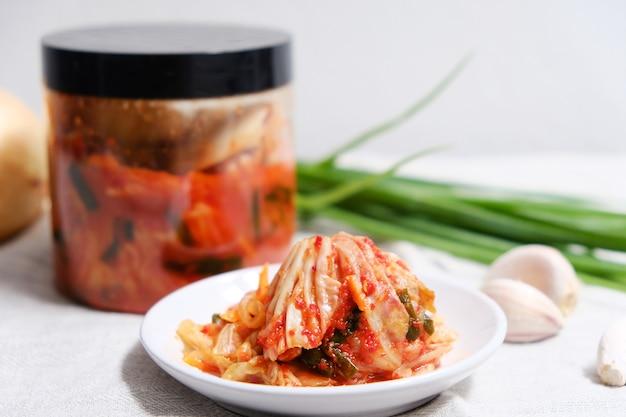 Il kimchi è posto in un piatto bianco con gli ingredienti sul tavolo