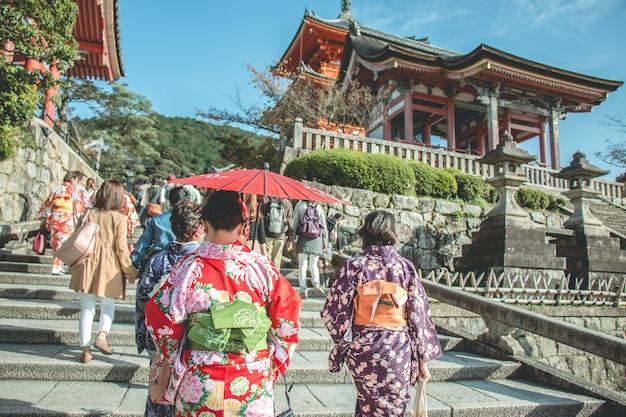 Il kimino da portare della donna cammina a kiyomizu dera, tempio
