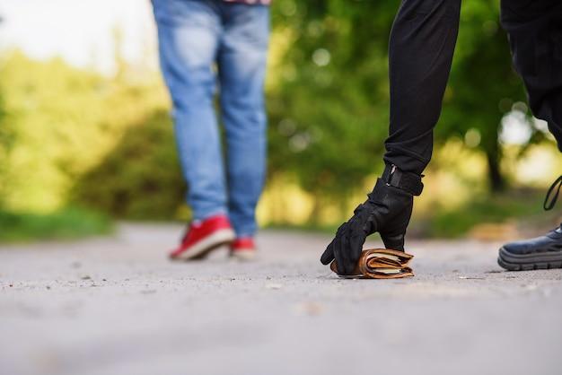 Il ladro in abiti neri solleva un portafoglio con soldi da terra. borseggi per strada durante il giorno.