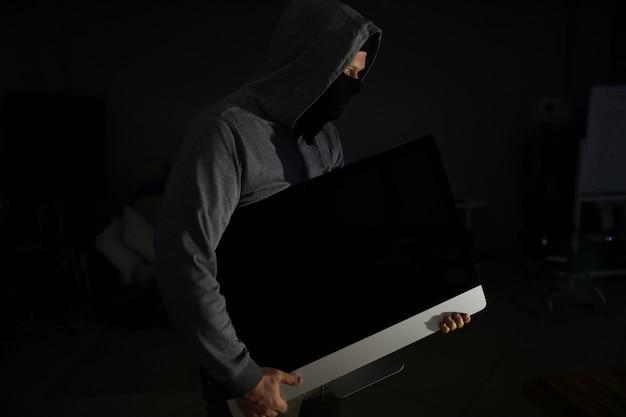 Il ladro in passamontagna trasporta il pc dall'appartamento delle vittime