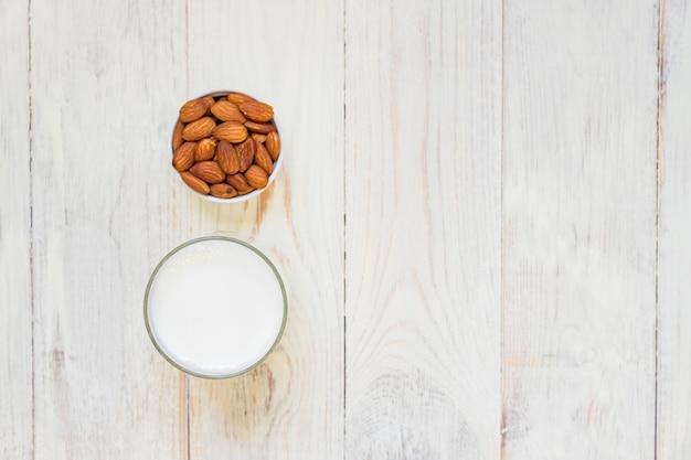 Il latte di mandorle casalingo in una bottiglia e le noci in porcellana bianca lanciano su fondo di legno. vista dall'alto, copia spazio