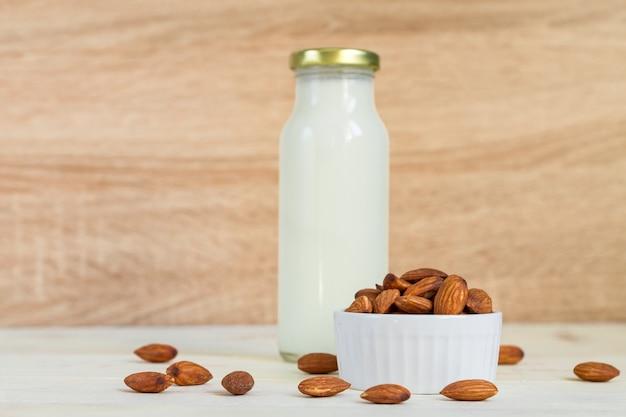 Il latte di mandorle casalingo in una bottiglia e le noci in porcellana bianca lanciano su fondo di legno