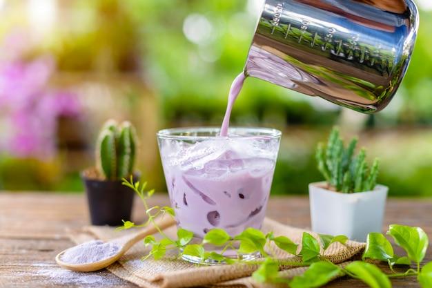 Il latte di taro porpora ghiacciato in vetro trasparente è servito sulla tavola di legno in caffè del giardino