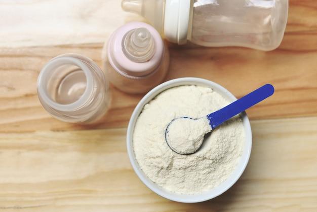 Il latte in polvere in cucchiaio con la lattina e biberon munge sulla tavola di legno