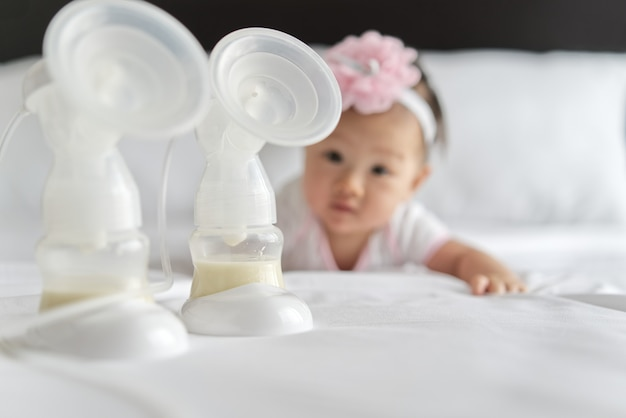 Il latte materno nelle bottiglie della pompa del latte sul letto con il piccolo bambino sveglio che striscia nel fondo.