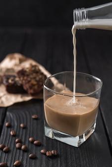 Il latte versato dalla bottiglia in un bicchiere di caffè