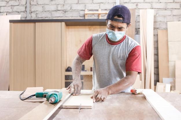 Il lavoratore all'area di lavoro del carpentiere che taglia il bordo di legno facendo uso della sega