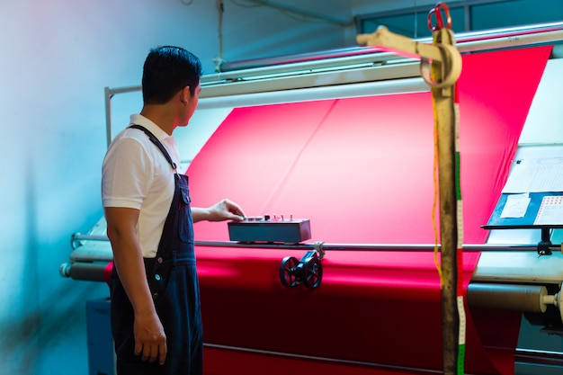 Il lavoratore asiatico controlla i tessuti in pianta tessile