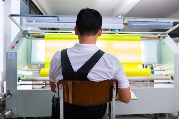 Il lavoratore asiatico controlla i tessuti nella fabbrica tessile