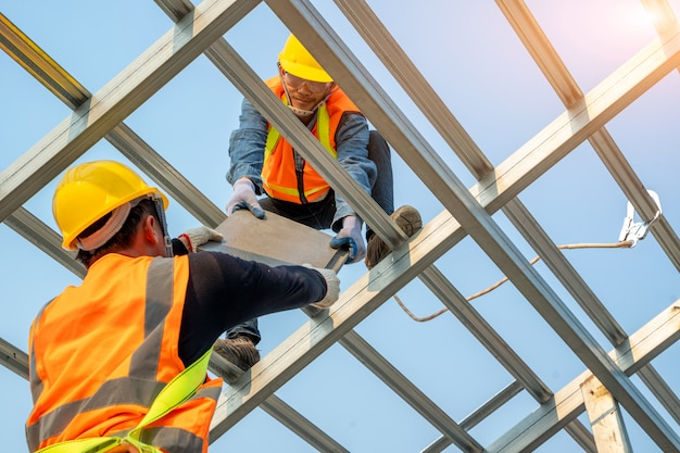 Il lavoratore degli ingegneri installa il nuovo tetto al cantiere, gli strumenti del tetto, il tecnico del tetto di cpac, i concetti della costruzione.