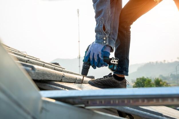 Il lavoratore degli ingegneri installa il nuovo tetto di cpac, gli strumenti del tetto, il trapano elettrico usato sui nuovi tetti con il tetto di cpac, i concetti della costruzione.