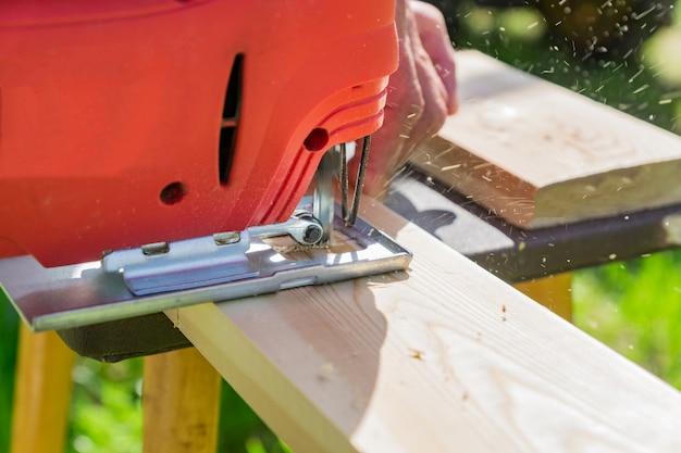Il lavoratore del legno che taglia il pannello di legno con la maschera ha visto all'aperto, punto di vista del primo piano dell'uomo che lavora con il puzzle elettrico e la plancia di legno