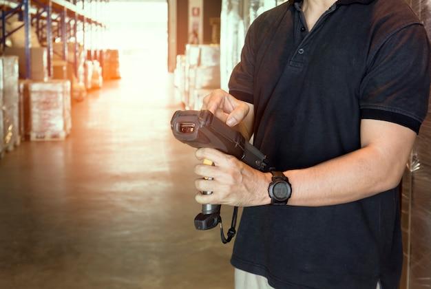 Il lavoratore del magazzino sta tenendo lo scanner del codice a barre con l'inventario dei prodotti in magazzino.