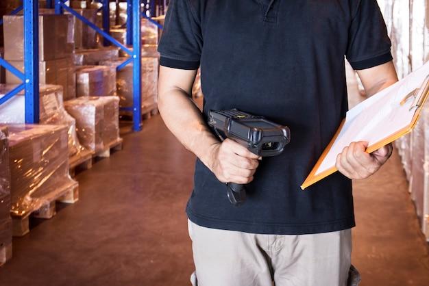 Il lavoratore del magazzino sta tenendo lo scanner del codice a barre e gli appunti che funzionano con l'inventario nel magazzino del magazzino.