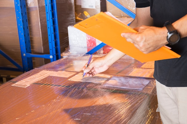 Il lavoratore del magazzino sta tenendo una lavagna per appunti con l'inventario del prodotto.