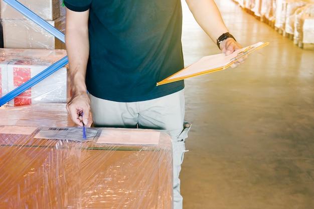 Il lavoratore del magazzino sta tenendo una lavagna per appunti con l'inventario il prodotto in magazzino.