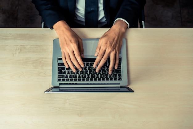 Il lavoratore dell'uomo d'affari utilizza un computer portatile.