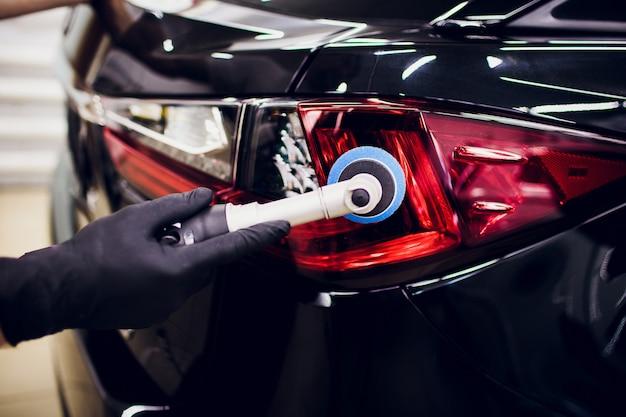Il lavoratore della cera della lucidatura dell'automobile passa la tenuta del lucidatore e dei dettagli polacchi dell'automobile o valeting l'automobile rossa di fanale posteriore di concetto
