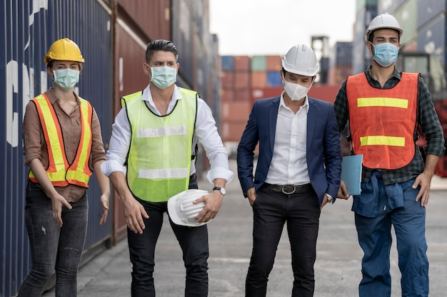Il lavoratore della gente del gruppo indossa la maschera di protezione per il viso e il casco di sicurezza e indossa un abito di sicurezza