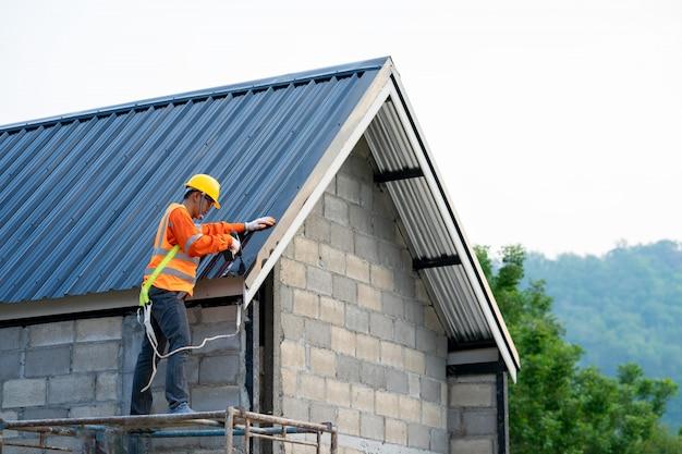 Il lavoratore di costruzione che indossa l'imbracatura di sicurezza sta installando il nuovo tetto, concetto di edificio residenziale in costruzione.
