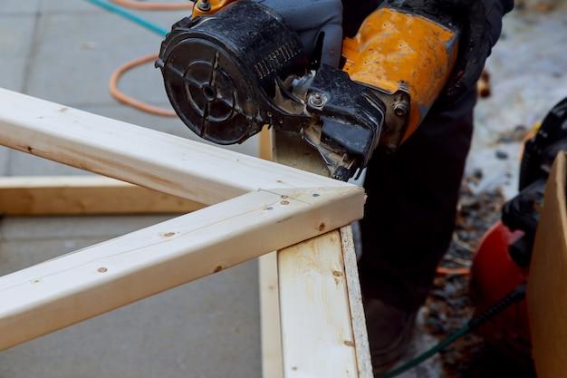 Il lavoratore esegue lavori di finitura delle pareti con una tavola di legno bianca, utilizzando il livello della linea laser.