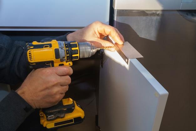 Il lavoratore imposta una nuova maniglia sul mobile bianco con un cacciavite che installa i mobili della cucina
