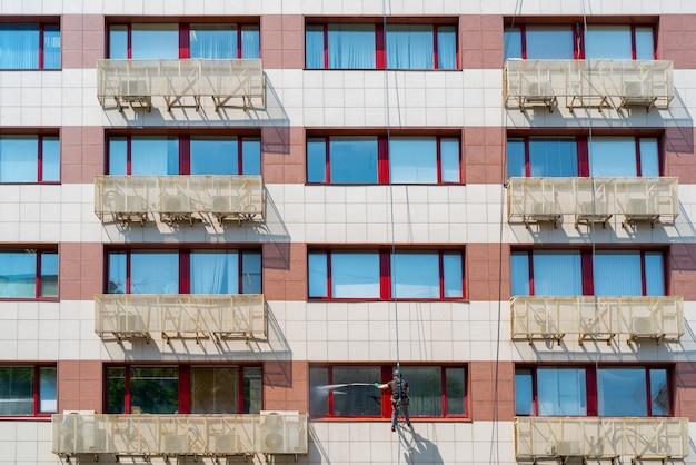 Il lavoratore lava le finestre in un edificio per uffici