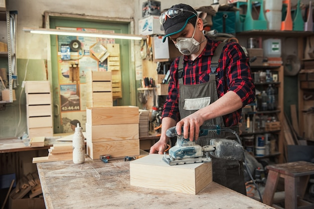 Il lavoratore macina la scatola di legno