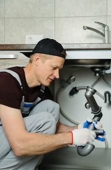 Il lavoratore mette la trappola per il lavello della cucina