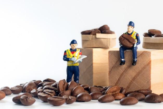 Il lavoratore miniatura che si siede sul blocco di legno mentre porta il chicco di caffè e sotto ha i chicchi di caffè con il lavoratore che controlla i prodotti