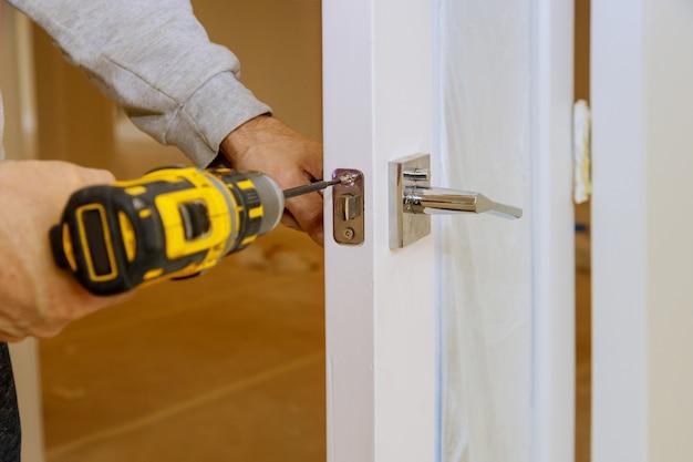 Il lavoratore monta della serratura nella porta di legno