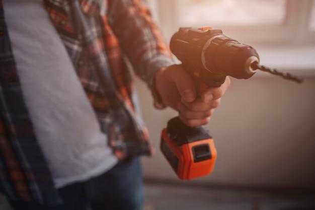 Il lavoratore o il costruttore tiene un trapano elettrico. concetto di costruzione o riparazione. sullo sfondo della costruzione