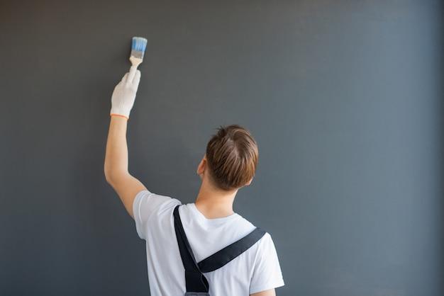 Il lavoratore sta con la schiena e dipinge un muro su uno sfondo grigio