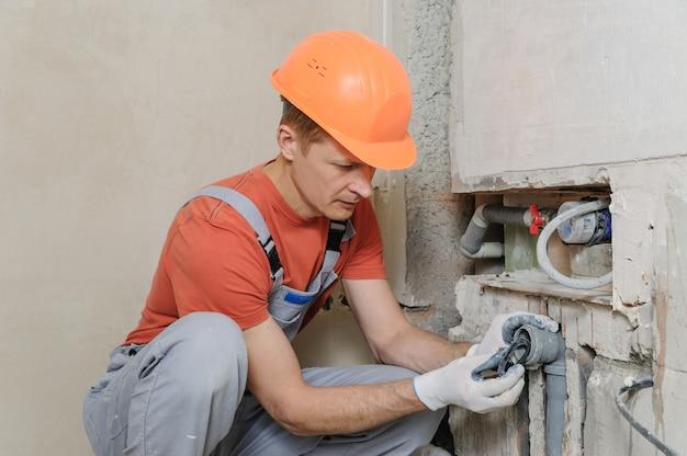 Il lavoratore sta installando i tubi per fognatura.