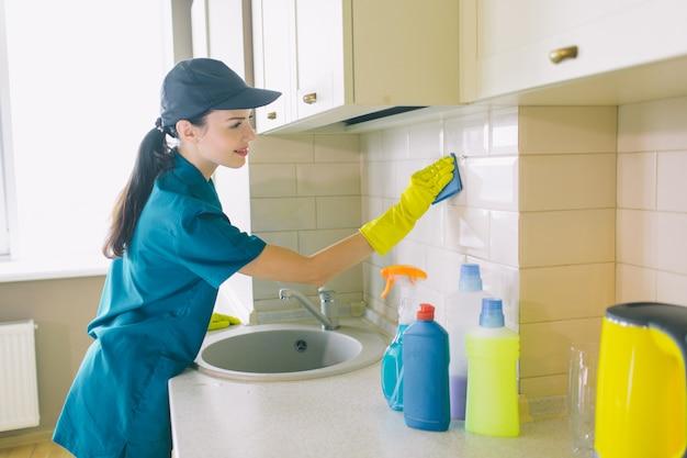 Il lavoratore sta pulendo le piastrelle con la spugna