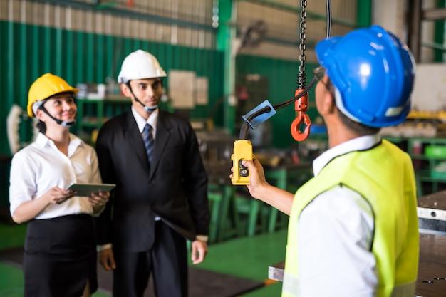 Il lavoratore usa il telecomando per sollevare la gru in fabbrica