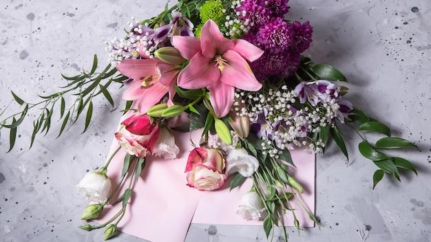 Il lavoro del fiorista nel processo di creazione di un bouquet con gigli sul posto di lavoro