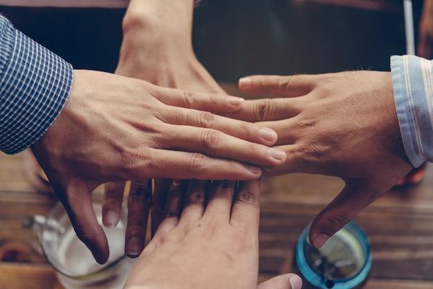 Il lavoro di squadra della squadra unisce il concetto di associazione delle mani gli amici si uniscono la mano insieme.