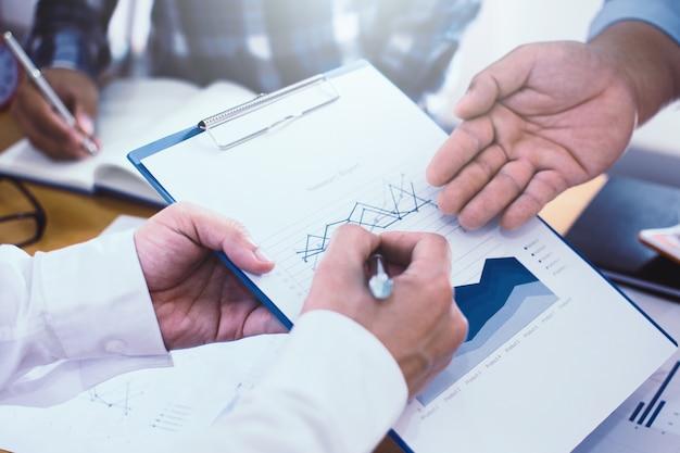 Il leader del team di uomini d'affari sta discutendo i dati del piano di marketing e i risultati finanziari