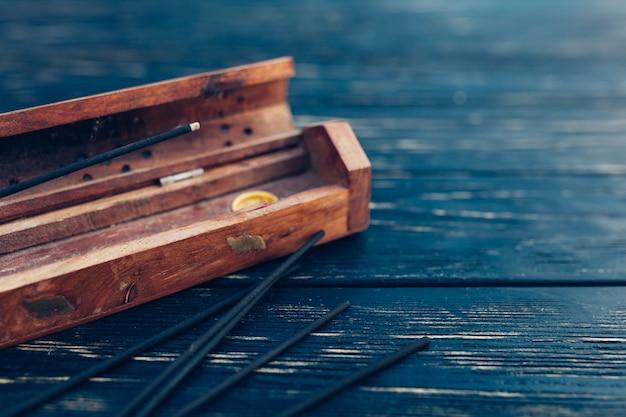 Il legno di sandalo attacca su un tavolo di legno nero. cultura asiatica tradizionale. aromaterapia