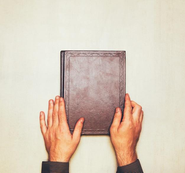 Il libro è nelle mani di un uomo dall'alto. mock up per testo, congratulazioni, frasi, lettering