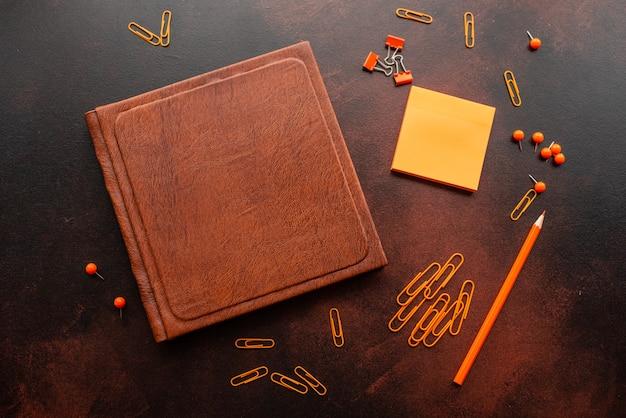 Il libro, la matita, le graffette e i fogli per i segni giacciono su un desktop