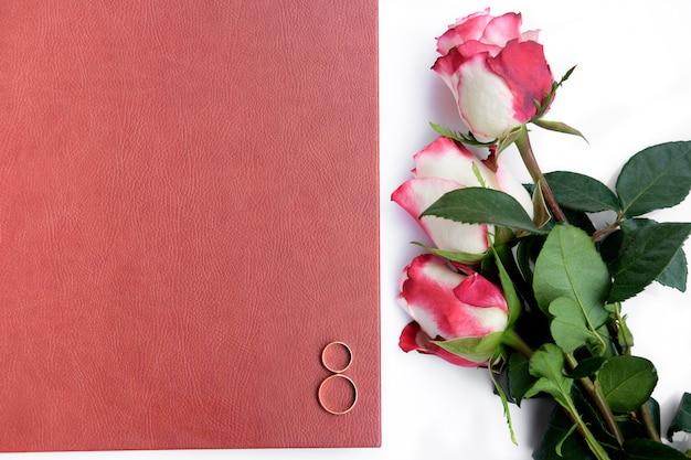 Il libro o l'album di nozze coperto di cuoio rosso con due fedi nuziali e tre rose si trova su fondo bianco.